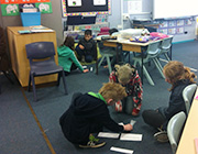 Kids do exercises on the floor in Tidbinbilla classroom